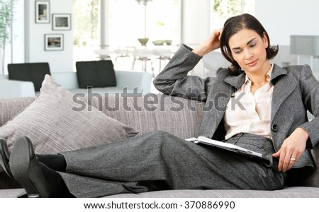 Mid adult caucasian businesswoman in suit lying on sofa with personal business organizer at home, thinking. Small smile. - stock photo