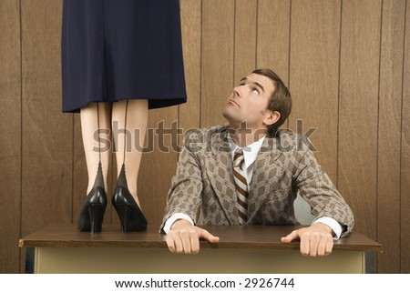 Mid-adult Caucasian male holding desk looking up to Caucasian female standing on desk.