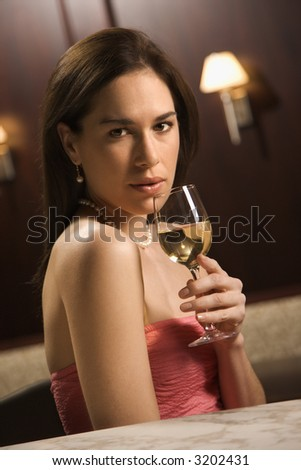 Mid adult Caucasian woman sitting at bar with glass of white wine looking at viewer. - stock photo
