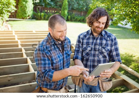 Mid adult construction worker pointing at digital tablet while discussing project with coworker - stock photo