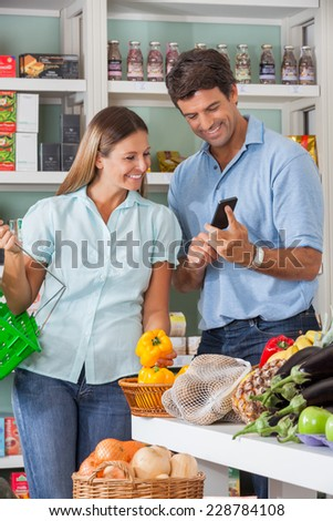 Mid adult couple checking list on mobilephone while shopping in supermarket - stock photo