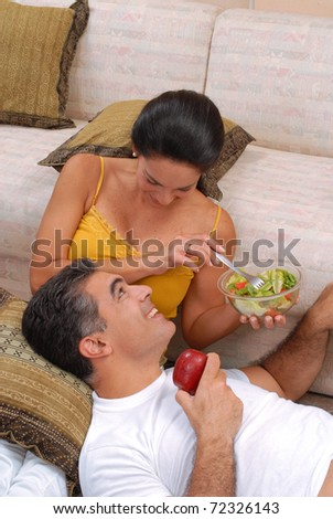 Mid adult couple eating salad and fruit in a living room. - stock photo