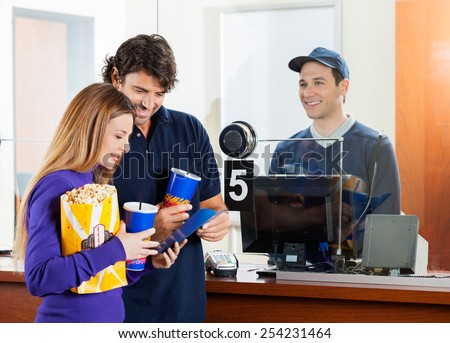 Mid adult couple holding snacks while buying movie tickets at box office - stock photo