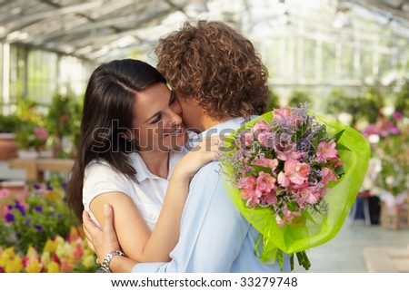 mid adult couple hugging in flower nursery and holding bouquet - stock photo