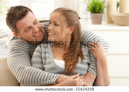 Mid-adult couple looking at each other hugging in living room, smiling. - stock photo