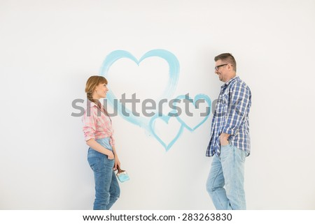 Mid-adult couple looking at each other with painted heart on wall - stock photo