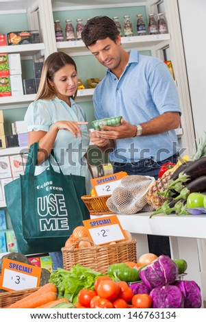 Mid adult couple reading product details while shopping vegetables in supermarket - stock photo