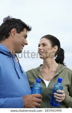 Mid adult couple with water bottles - stock photo