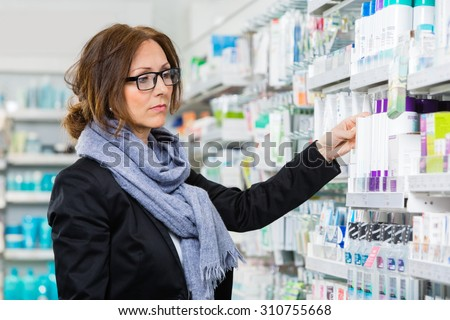 Mid adult female consumer choosing product in pharmacy - stock photo