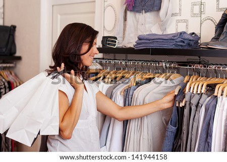 Mid adult female customer choosing clothes from rack in clothing store - stock photo