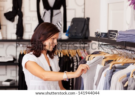 Mid adult female customer looking at clothes in clothing store - stock photo