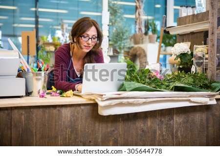 Mid adult female florist using laptop at counter in flower shop - stock photo