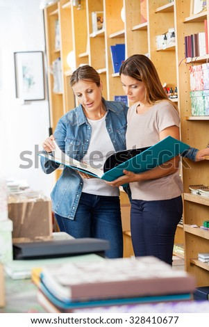Mid adult female friends looking at large book in store