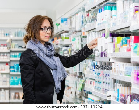 Mid adult female purchaser choosing product in pharmacy - stock photo