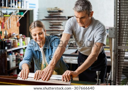 Mid adult female worker assisting male colleague to use squeegee in factory - stock photo