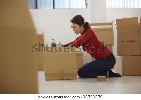 mid adult happy woman during move with boxes at new flat and packing carton - stock photo