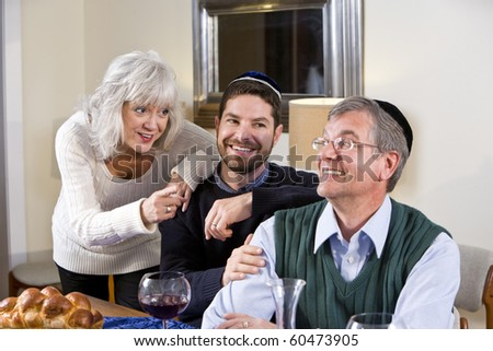 Mid-adult Jewish man at home smiling with senior parents