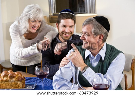 Mid-adult Jewish man at home smiling with senior parents - stock photo