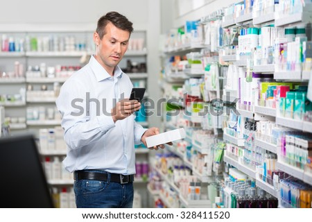 Mid adult male customer checking information on mobile phone while holding product in pharmacy - stock photo