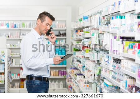 Mid adult male customer using mobile phone and digital tablet in pharmacy - stock photo