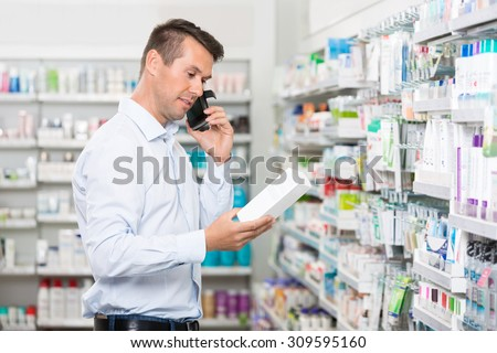Mid adult male customer using mobile phone while holding product in pharmacy - stock photo