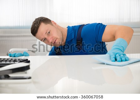 Mid adult male janitor cleaning desk with sponge at office - stock photo