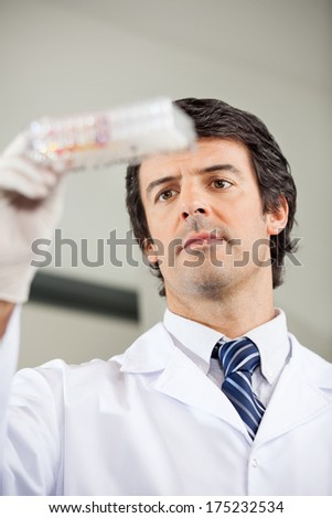 Mid adult male researcher analyzing microplate in laboratory - stock photo