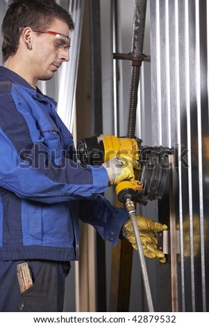 mid adult man at workshop working with nail gun on construction - stock photo