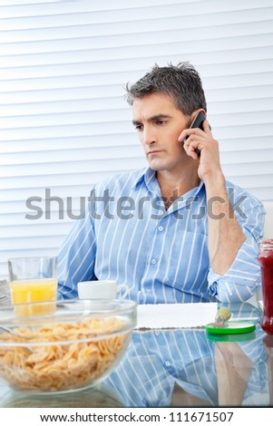 Mid adult man attending phone call while having breakfast at the table
