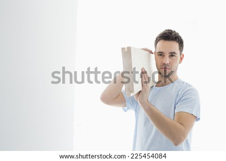 Mid-adult man carrying lumber on shoulder - stock photo
