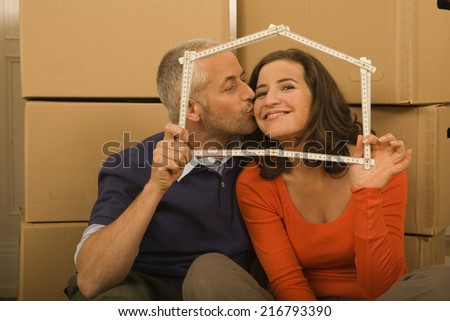 Mid adult man kissing a young woman and holding a scale in the shape of a house - stock photo