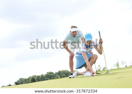 Mid-adult man looking at woman aiming ball on golf course - stock photo