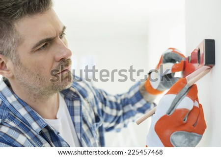 Mid-adult man marking on wall with level - stock photo