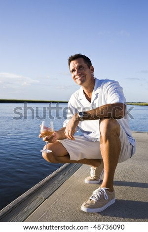 Mid-adult man on dock by water enjoying drink on sunny day