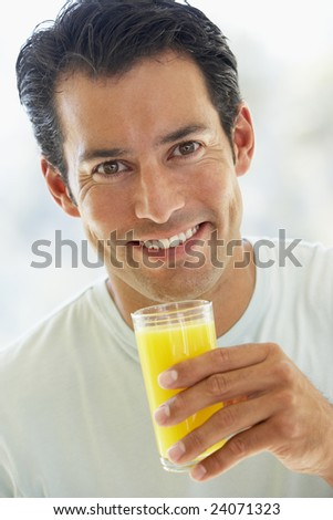 Mid Adult Man Smiling At The Camera And Drinking Orange Juice - stock photo