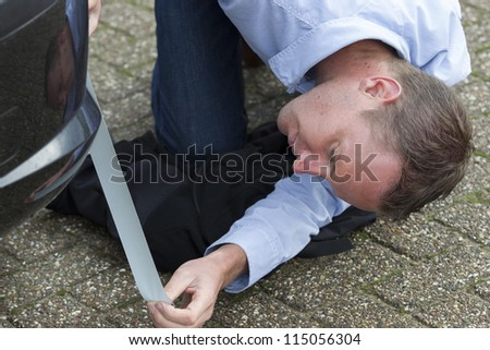 Mid adult man using duct tape to fix his car. Horizontal shot. - stock photo