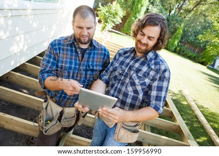 Mid adult manual workers discussing project on digital tablet at construction site - stock photo