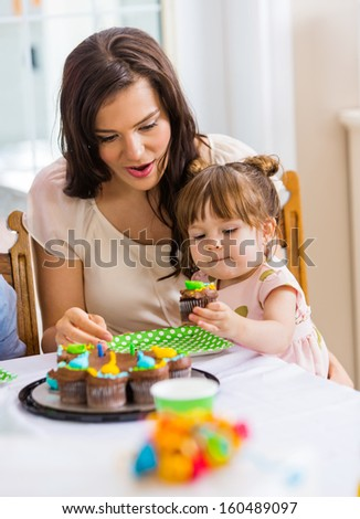 Mid adult mother with girl eating cupcake at birthday party