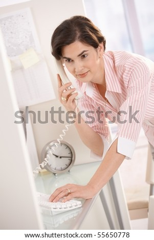 Mid-adult office worker on landline phone call, working on computer, smiling.