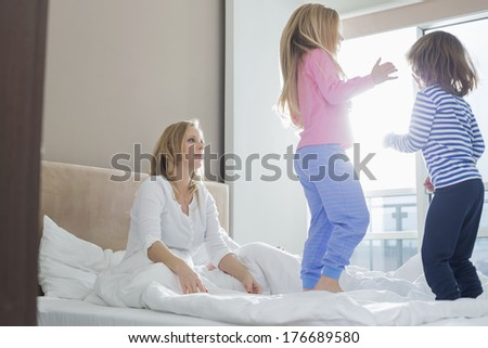Mid adult parents looking at playful children in bedroom - stock photo