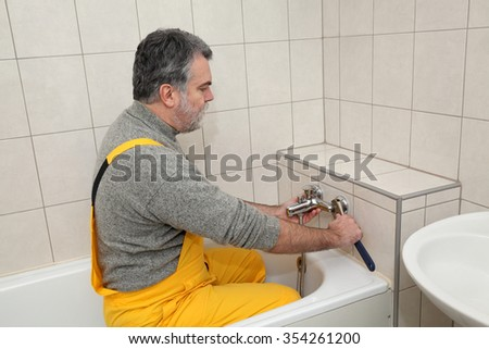 Mid adult plumber fixing water  tap at bath tube in a bathroom - stock photo