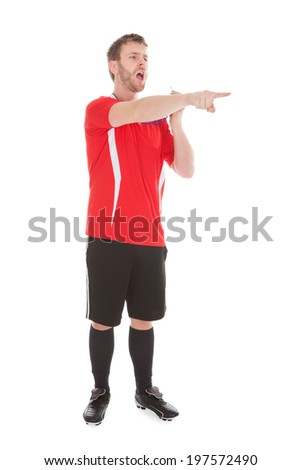 Mid adult referee pointing while holding whistle over white background - stock photo
