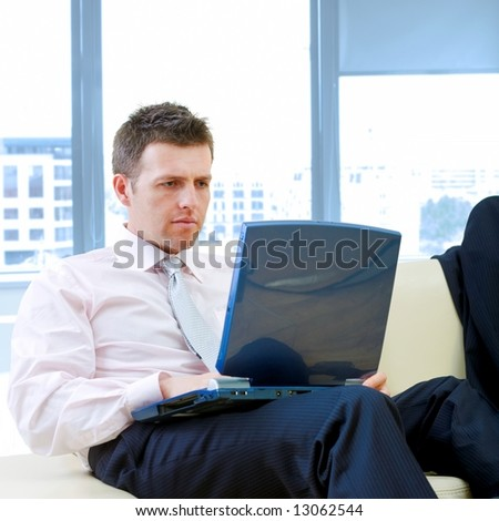 Mid-adult serious businessman sitting on couch at office and working on laptop computer.