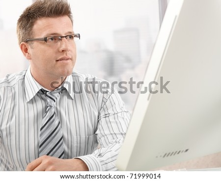 Mid-adult smart businessman looking at computer screen in office? - stock photo