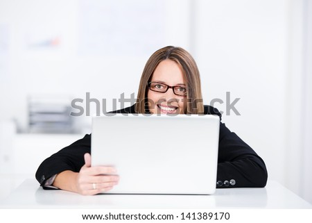Mid adult smiling businesswoman with laptop in office - stock photo