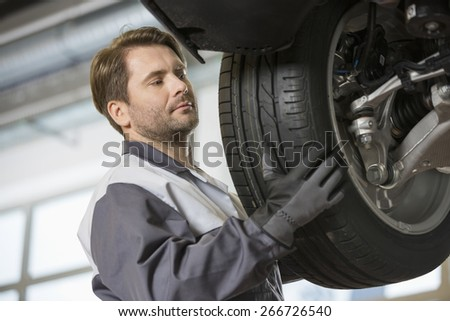 Mid adult technician adjusting car's tire in workshop - stock photo
