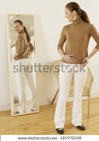 Mid-Adult Trying on Jeans in Mirror - stock photo