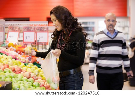Mid adult woman buying fruit at a supermarket - stock photo