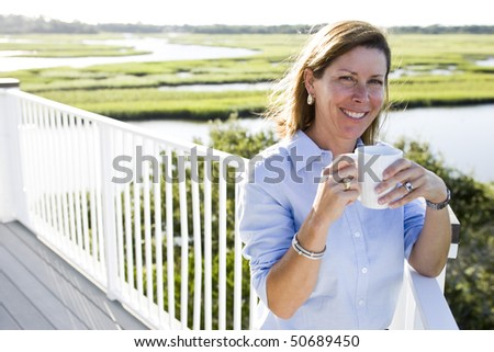 Mid-adult woman having cup of coffee on terrace on vacation with scenic view - stock photo