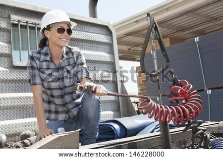 Mid adult woman holding a break hose of a flatbed truck - stock photo